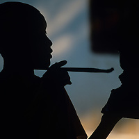 Asia, Laos, Luang Prabang,  Silhouette of young Buddhist Monk crafting traditional bowl Wat Xieng Muan Temple's arts school