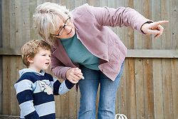 Young boy arriving at nursery with his grandmother,
