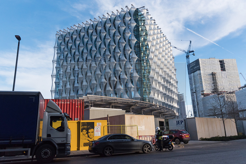 © Licensed to London News Pictures. 19/12/2017. London, UK. A parking ticket attendant issues a ticket for a ca parked outside the new United States Embassy in Wandsworth, South London. At a cost of over £750 million, the new embassy is the most expensive in the world and features a security moat and gardens on each floor. It is reported the US President Donald Trump will officially open the embassy in early 2018. Photo credit: Ray Tang/LNP