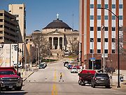 "31 MARCH 2020 - DES MOINES, IOWA: A man crosses an empty street on a warm spring day in downtown Des Moines. Despite the pleasant weather, many people stayed indoors because the coronavirus (SARS-CoV-2) pandemic. On Saturday morning, 04 April, Iowa reported 786 confirmed cases of the Novel Coronavirus (SARS-CoV-2) and COVID-19. There have been 14 deaths attributed to COVID-19 in Iowa. Restaurants, bars, movie theaters, places that draw crowds are closed until 30 April. The Governor has not ordered ""shelter in place"" but several Mayors, including the Mayor of Des Moines, have asked residents to stay in their homes for all but the essential needs. People are being encouraged to practice ""social distancing"" and many businesses are requiring or encouraging employees to telecommute.         PHOTO BY JACK KURTZ         PHOTO BY JACK KURTZ"