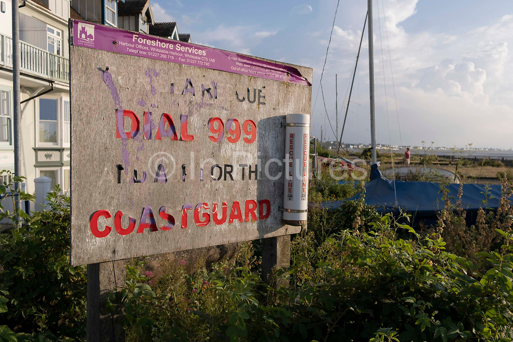 A fading Coastguard emergency 999 sign on a shingle beach, on 25th July 2021, in Whitstable, Kent, England.