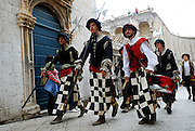 Six men dressed in traditional period costume walk through the streets of Dobrovnik old town, Croatia