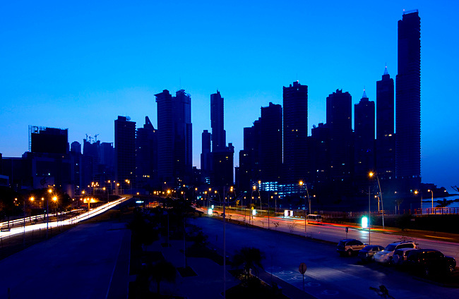 The blue light of dawn silhouettes the growing skyline of Panama City, Panama.