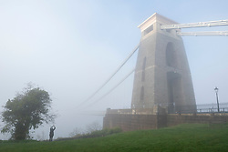 © Licensed to London News Pictures; 27/11/2020; Bristol, UK. People look and take photos of the Clifton Suspension Bridge in winter fog during the Covid-19 lockdown in England during the coronavirus pandemic. Bristol with one of the highest rates of Covid-19 infection in the country has been placed in the highest risk category of tier 3 to come into effect after lockdown ends on 02 December. Photo credit: Simon Chapman/LNP.
