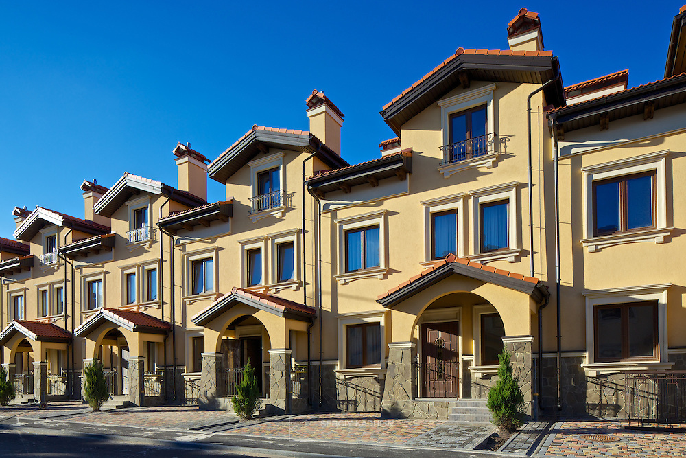 """Architectural details of residential real estate development project """"Italian Village"""" in Kyiv, Ukraine. Exterior view of townhouses in the daylight and blue sky."""