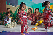 Young Nepalese malnourished children in the play room of Friends of Needy Children Nutritional Rehabilitation Home Kathmandu, Nepal.  They are wearing hospital pajamas and playing with toys. Some of the children's mothers are sitting behind the children. The centre treats malnourished children and provides education to mothers about nutrition and childcare. The children are encouraged to play between feeding sessions.