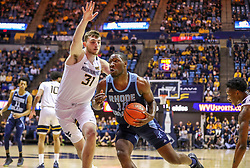 Dec 1, 2019; Morgantown, WV, USA; Rhode Island Rams forward Cyril Langevine (10) drives against West Virginia Mountaineers forward Logan Routt (31) during the first half at WVU Coliseum. Mandatory Credit: Ben Queen-USA TODAY Sports