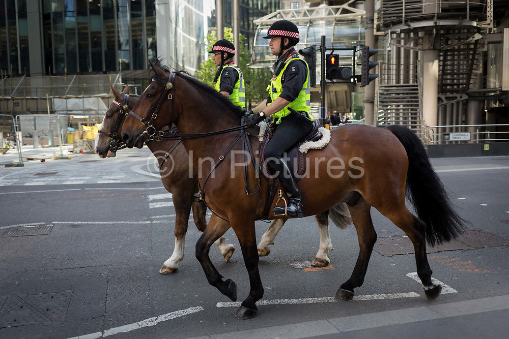 Mounted City police officers patrol Leadenhall in the City of London - the capitals financial district, on 6th June 2018, in London, England.
