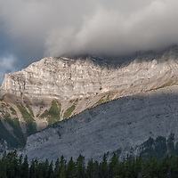 Early morning light illuminates Cascade Mountain as clouds build over its summit.  Banff National Park, Alberta, Canada.
