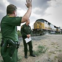 Verenigde Staten.Arizona.Nogales.juli 2005.<br /> Grenspolitie arresteert illegale vluchtelingen in de woestijn van Zuid Arizona, die illegaal vanuit Mexico de Verenigde Staten zijn binnengekomen. Ze worden gefoullerd op wapens en hun papieren worden gecontroleerd. Daarna worden de illegalen naar het hoofdbureau van de grenspolitie getransporteerd, waarna ze geregistreerd worden alvorens ze terug de grens overgebracht worden.Body check.Controle.Border Patrol.Mexicaan.Grens.Grens problematiek.<br /> Op de foto zwaait de Border Patrol naar een tegemoetkomende trein.Langs het spoor bevinden zich regelmatig Mexicaanse illegalen die op deze manier hun weg naar Tuscon of Phoenix proberen te vinden.