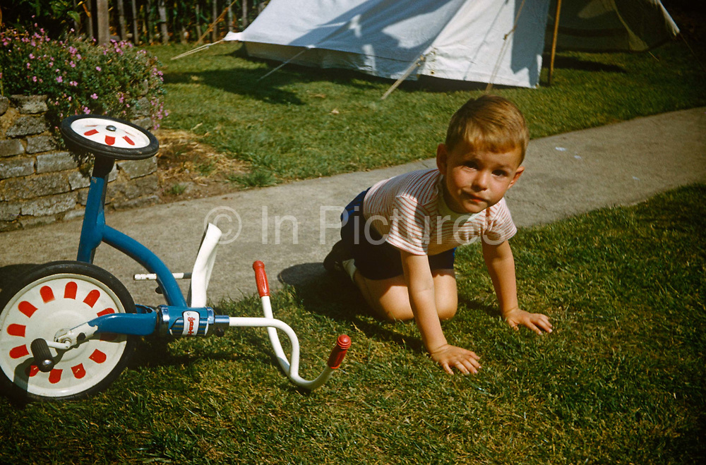 A young boy sits on the lawn after falling from his tricycle on a summer's day in the family garden in the early nineteen sixties. Sitting on his knees on the soft summer grass the young lad looks brave rather than tearful. There is the family tent erected across from the path, its open flaps perhaps drying out after rain or simply as a play den for the boy. The picture was recorded on Kodachrome (Kodak) film in about 1964.