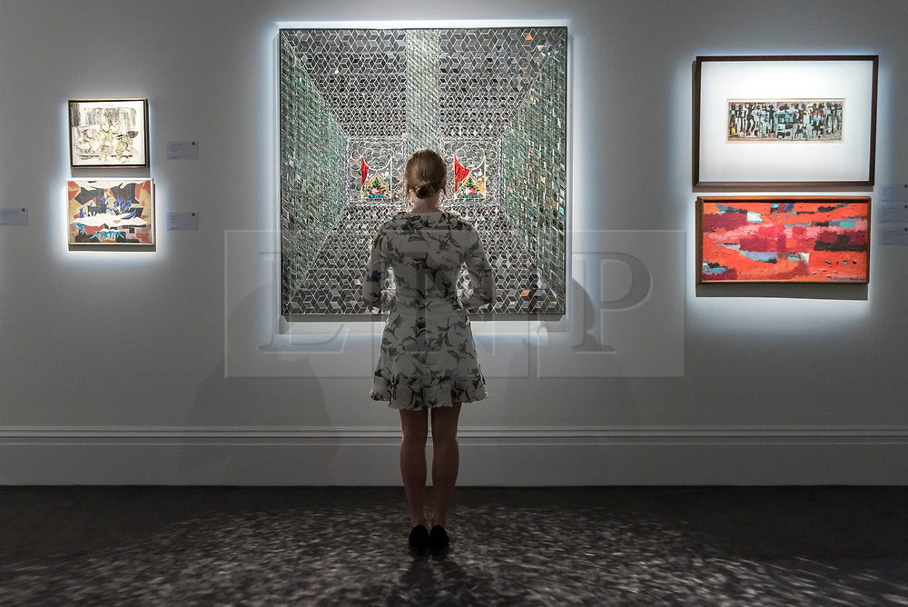 """© Licensed to London News Pictures. 20/04/2018. LONDON, UK. A staff member views (C) """"Recollections I"""", 2008, by Monir Farmanfarmaian (Est. GBP160-200k) at a preview of works in Sotheby's 20th Century Middle East, Orientalist and Islamic upcoming art sales in New Bond Street.  The works will be sold at auction in the last week of April.    Photo credit: Stephen Chung/LNP"""