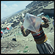 A boys holds a kite made of a plastic bag in Kabul.