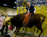 Omaha, Neb 5/6/06 Warren Buffet sits atop a bull at the Justin Boots booth on the floor at the Berkshire Hathaway annual meeting in the Qwest Center Omaha Saturday Morning.(Chris Machian/Prairie Pixel Group)