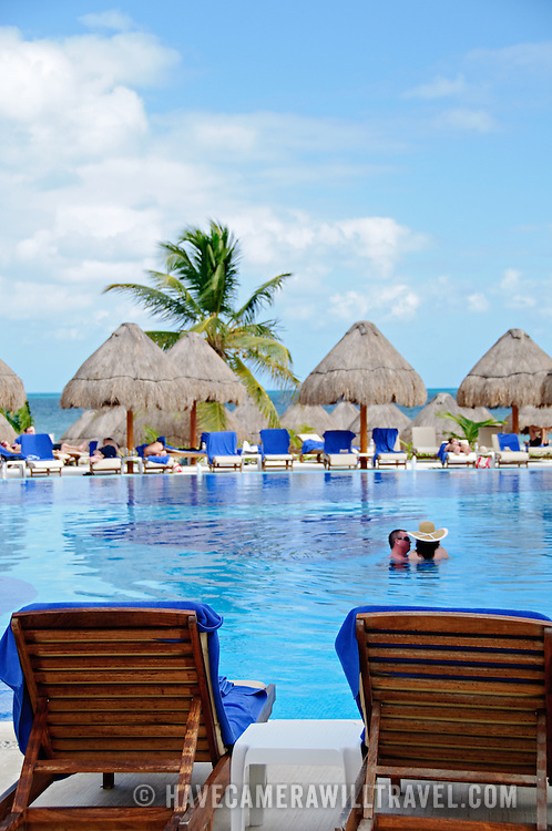 A couple enjoys the water of a pool at Excellence Playa Mujeres Resort at Playa Mujeres, north of Cancun, Quintana Roo, Mexico