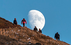 Walkers head toward the rising moon during the last minutes of day light over the Crags in Edinburgh