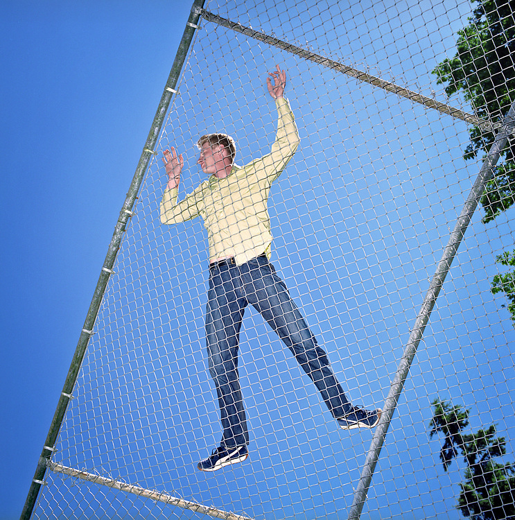 Young man lying down on chain link fence enclosure