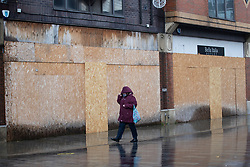 © Licensed to London News Pictures. 03/11/2020. St Helens, UK. A woman walks past a boarded up business as people brave the rain in St Helens to do some shopping. Photo credit: Kerry Elsworth/LNP