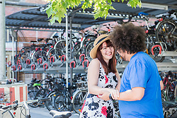 Happy young couple at bicycle parking