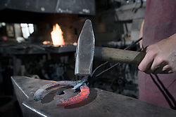 Apprentice blacksmith hammering red hot horseshoe on anvil at workshop, Bavaria, Germany