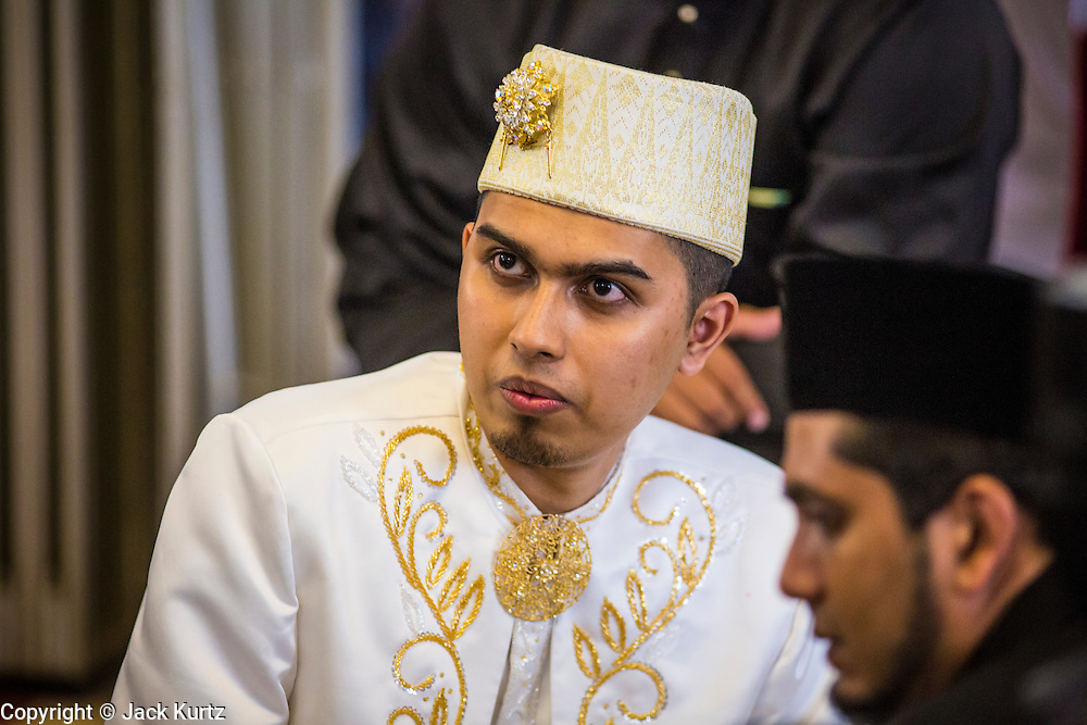 22 DECEMBER 2012 - SINGAPORE, SINGAPORE:  A groom at a wedding in the Sultan Mosque in Singapore. The Sultan Mosque is the focal point of the historic Kampong Glam area of Singapore. Also known as Masjid Sultan, it was named for Sultan Hussein Shah. The mosque was originally built in the 1820s. The original structure was demolished in 1924 to make way for the current building, which was completed in 1928. The mosque holds great significance for the Muslim community, and is considered the national mosque of Singapore. It was designated a national monument in 1975.           PHOTO BY JACK KURTZ