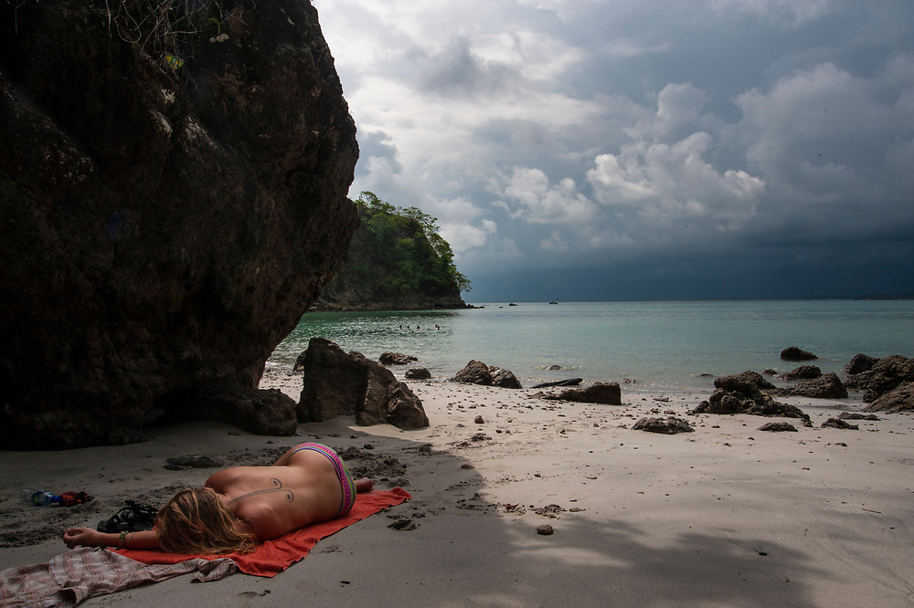 A woman naps on the beach on a humid day in Costa Rica.