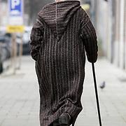 NLD/Amsterdam/20080221 - Oude Marokaanse man in traditionele kleding lopend over straat in Amsterdam met een wandelstok