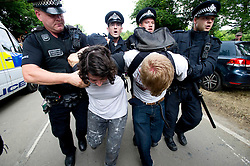 © London News Pictures. 19/08/2013. Balcombe, UK. A woman (left) and man (right) being arrested by police as activists clash with police outside to the Cuadrilla drilling site in Balcombe, West Sussex on a day of of civil disobedience organised by campaign group No Dash For Gas. Cuadrilla has temporarily ceased drilling at the site, which has been earmarked for fracking, under advice from the police. Photo credit: Ben Cawthra/LNP