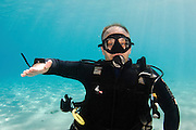 Underwater Hand signs scuba diver demonstrates the sign language for divers. Something is wrong: An open hand with palm down and fingers apart is rocked back and forth on the axis of the forearm.
