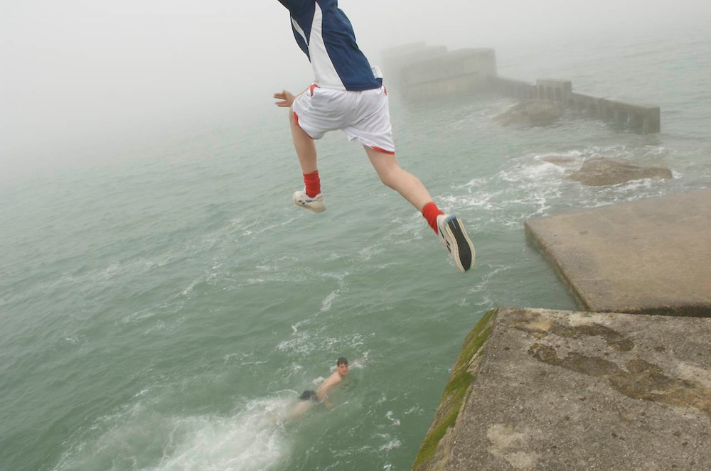 Teens leap from a pier on the Southeast coast of England.