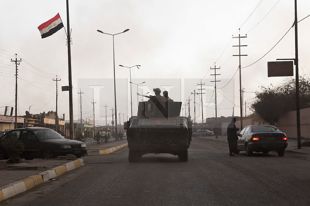 Licensed to London News Pictures. 02/11/2016. Qayyarah, Iraq. With the sky blotted out by burning oil wells, set alight by retreating Islamic State militants, soldiers of the Iraqi Army's Emergency Response Unit keep watch from the top of their armed Humvee utility vehicle as their convoy drives through the main street of Qayyarah, Iraq.<br /> <br /> Two months after being liberated from the Islamic State, the Iraqi town of Qayyarah, located around 30km south of Mosul, is still dealing with the environmental repercussions of their ISIS occupation. The town's estimated 15,000 inhabitants constantly live under, and in, heavy clouds of smoke which often envelope the settlement. The clouds emanate from burning oil wells in a nearby oil field that were set alight by retreating ISIS extremists after a two year occupation. The proximity of the fires, often right next to homes within the town, covers many buildings and residents with thick soot and will lead to long term health and environmental implications. Photo credit: Matt Cetti-Roberts/LNP