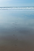 Waves crashing onto the beach and footprints in the sand at Woolacombe, North Devon, UK