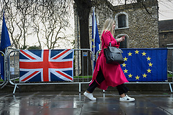 © Licensed to London News Pictures. 18/03/2019. LONDON, UK.  A woman walks by the UK flag and Europe flag outside the Houses of Parliament.  Theresa May, Prime Minister, is considering requesting the European Union for a long delay to article 50 if she determines that MPs will reject her Brexit deal in a meaningful vote for a third time..  Photo credit: Stephen Chung/LNP