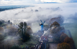 © Licensed to London News Pictures. 14/11/2019. Shipley, UK. Mist clings to the landscape as the sun rises over King's Mill windmill in Shipley, West Sussex. Environment Agency flood warning alerts are in place for some homes and businesses in West Sussex after a night of heavy rain. Photo credit: Peter Macdiarmid/LNP