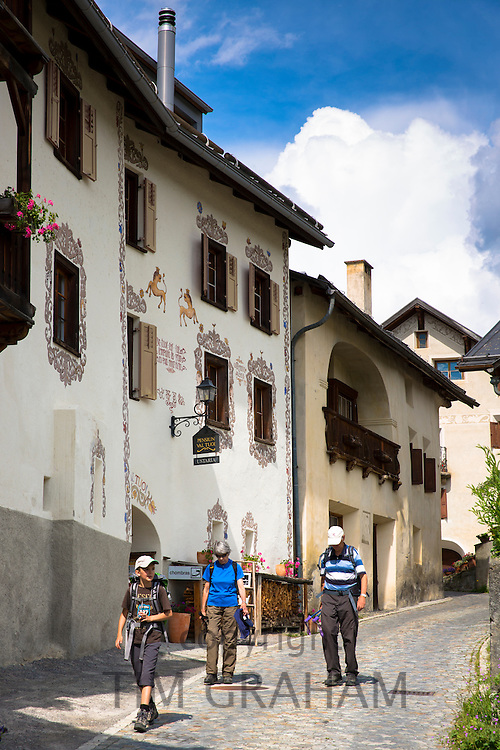 Tourists pass Pension Val Tuoi in the Engadine Valley in village of Guarda with painted stone 17th Century houses, Switzerland