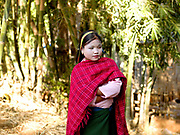 A Pa'O ethnic minority girl wearing thanakha (a traditional Burmese sunscreen and moisturiser), and a brightly coloured, handwoven skarf,  Shan State, Myanmar (Burma)