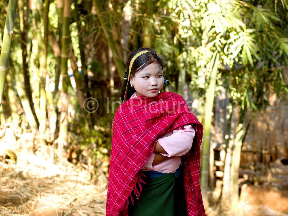 A Pa'O ethnic minority girl wearing thanakha (a traditional Burmese sunscreen and moisturiser), and a brightly coloured, handwoven skarf,  Shan State, Myanmar (Burma)