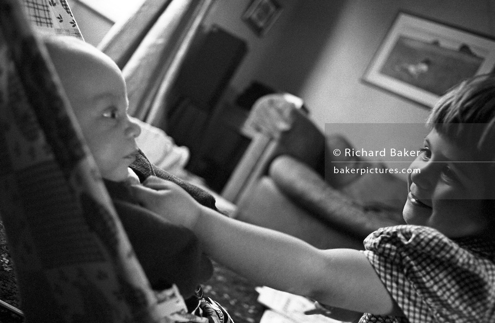 """A two and half year-old girl shows affection to her baby brother in the living room of her South London home. Reaching out to show her love, the big sister tickles the boy under his chin although he looks more intrigued than amused at the attention that this person is showing him. He is a few weeks old and lies in a baby bouncer chair on the floor. from a personal documentary project entitled """"Next of Kin"""" about the photographer's two children's early years spent in parallel universes. Model released."""