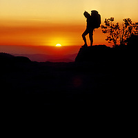 Yosemite National Park, California. A silhouette of a hiker atop Sentinel Dome at sunset.