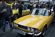 Yellow Triumph Stag vintage car on show at a monthly meet up in Greenwich Market in London, England, United Kingdom.