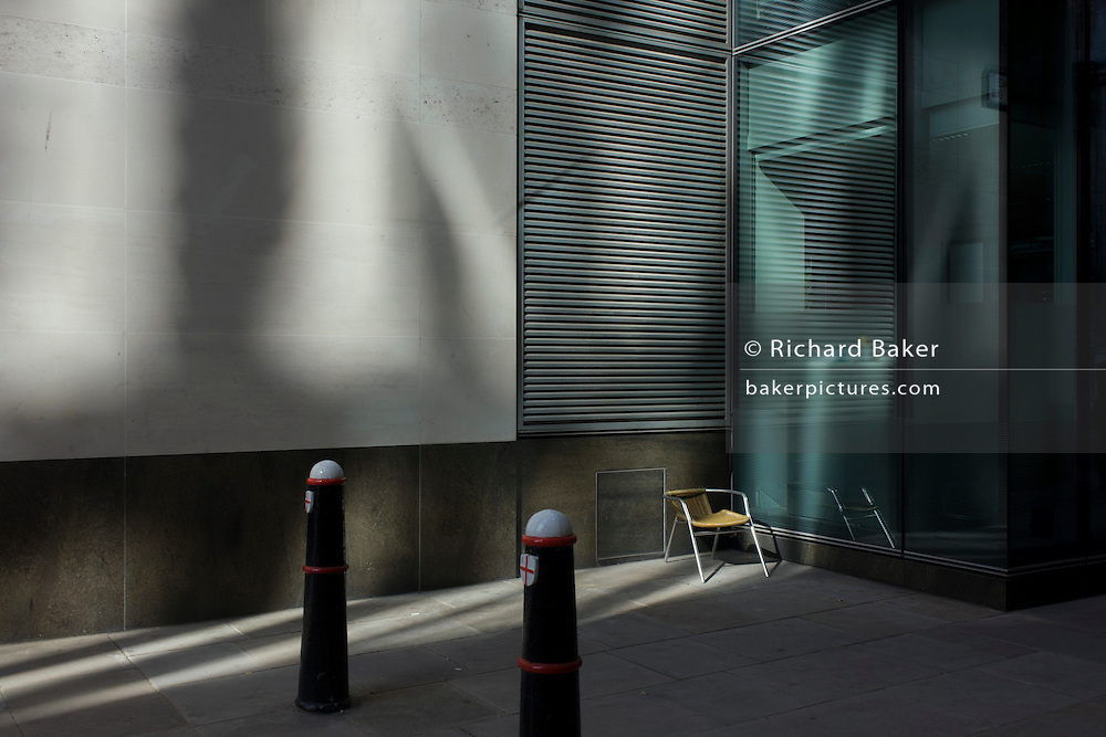 An empty seat in a sunlit corner of a City of London lane.