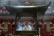 A woman dressed as a geisha , wearing a face-mask against COVID19, at the incense  burner in Senso-ji temple in Asakusa, Tokyo, Japan. Thursday February 18th 2021