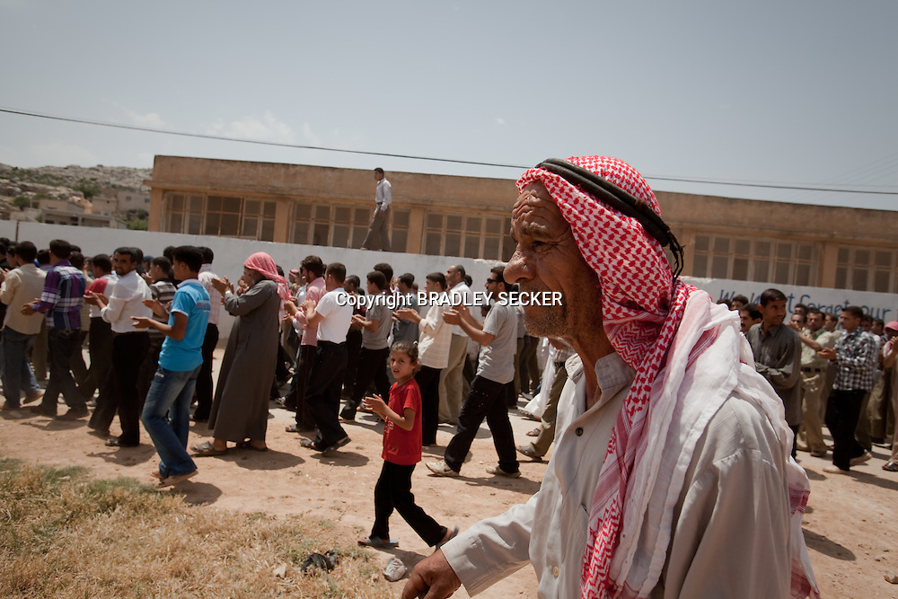 A village elder walks towards demonstrators at an anti-government protest in al-Basheria, Idlib, Syria. The weekly demonstrations call for the regime to step down, killings to end, and for democratic change in Syria. Basheria, Idlib, Syria. 15/06/2012