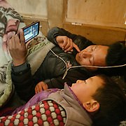 Watching wrestling on mobile phone. A modern day Layap house.