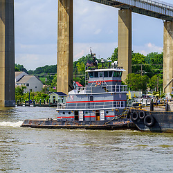 Chesapeake City, MD, USA - June 28. 2020: A tugboat pushes barges through the Chesapeake and Delaware Canal.