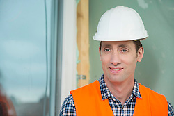 Portrait of construction worker with safety helmet at construction site of new building