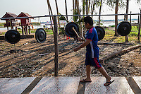 Banging Thai Temple Gongs for good luck at the island temple of Red Lotus Lake in Kumphawapi Udon Thani Thailand.