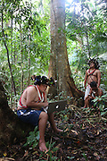 Chief Almir Narayamogo, with his apple computer, the other holds a gps reciever, they are mapping in the Surui territory, primary rainforest interior.<br /><br />An Amazonian tribal chief Almir Narayamogo, leader of 1350 Surui Indians in Rondônia, near Cacaol, Brazil, with a $100,000 bounty on his head, is fighting for the survival of his people and their forest, and using the world's modern hi-tech tools; computers, smartphones, Google Earth and digital forestry surveillance. So far their fight has been very effective, leading to a most promising and novel result. In 2013, Almir Narayamogo, led his people to be the first and unique indigenous tribe in the world to manage their own REDD+ carbon project and sell carbon credits to the industrial world. By marketing the CO2 capacity of 250 000 hectares of their virgin forest, the forty year old Surui, has ensured the preservation, as well as a future of his community. <br /><br />In 2009, the four clans and 25 Surui villages voted in favour of a total moratorium on logging and the carbon credits project. <br /><br />They still face deforestation problems, such as illegal logging, and gold mining which causes pollution of their river systems