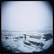 A man walks in am empty livestock market on a snowy day outside of Kabul.
