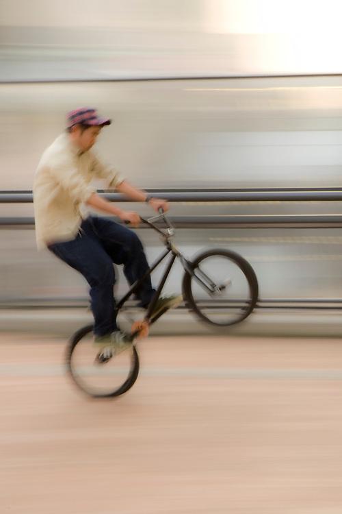 "Asia, Japan, Tokyo.  Teenager doing ""wheelie"" on bicycle (blurred motion)."